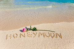 Inscription Honeymoon and rose on sea coast. On sand on sea coast an inscription Honeymoon and a blossoming rose Royalty Free Stock Photos