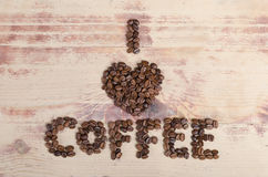 Inscription I love coffee from beans on wood Royalty Free Stock Photography