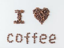 The inscription I love coffee written by roasted coffee beans on a white wooden table. The view from the top. Grains for the. The inscription I love coffee royalty free stock image