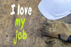 Inscription, I love my job, against the background of a white helmet of a builder with working gloves.  royalty free stock image