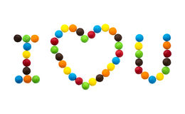 The inscription I love you and the Heart of multicolored round candies. Isolated on white background Royalty Free Stock Images