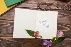 The inscription `I love you` in an open book with flowers, glasses near. royalty free stock photography