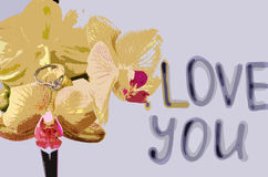 The inscription `I love you`. On the orchid is a gift - a wedding ring on the background of the inscription `I love you stock photo