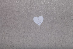 Inscription I LOVE YOU on paper heart on gray stone background Royalty Free Stock Image