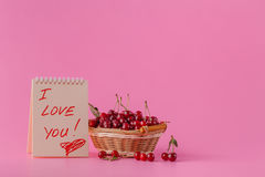 Inscription je t'aime avec des cerises sur le fond rose Photos libres de droits