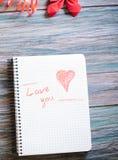Inscription je t'aime sur un bloc-notes blanc sur un fond en bois Images libres de droits