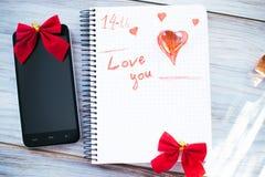 Inscription je t'aime sur un bloc-notes blanc sur un fond en bois Photo stock