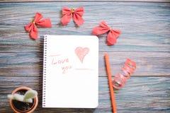Inscription je t'aime sur un bloc-notes blanc sur un fond en bois Photographie stock libre de droits