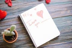 Inscription je t'aime sur un bloc-notes blanc sur un fond en bois Photos libres de droits