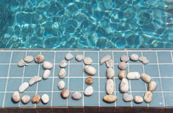 The inscription  2016  is laid out by pebble on a pool side Royalty Free Stock Image