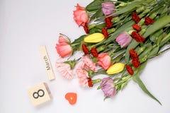 Inscription le 8 mars avec des fleurs sur un fond blanc Images stock