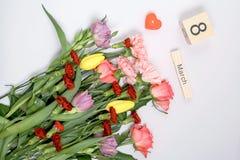 Inscription le 8 mars avec des fleurs sur un fond blanc Photographie stock