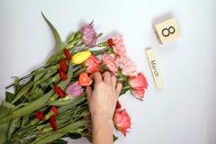 Inscription le 8 mars avec des fleurs sur un fond blanc Images libres de droits