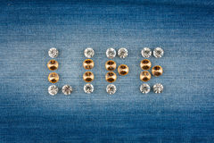 Inscription LIFE made of rhinestones, on jeans Royalty Free Stock Photography