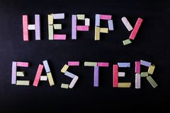 The inscription is lined with multicolored chalk on a black chalkboard, happy Easter. The concept of holiday and spring stock image