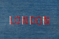 Inscription London, inlaid rhinestones on denim. Stock Photo