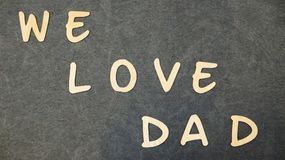 The inscription `We love dad ` folded of wooden letters on a black table. stock photos