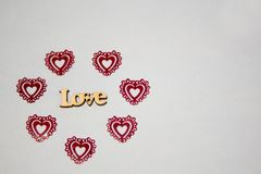 Inscription Love in an environment of red hearts on a light background royalty free stock image