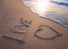 The inscription. Love and a heart drawn in the sand on the beach Stock Photo