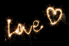 Inscription Love and heart of sparklers. Royalty Free Stock Photo
