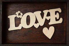 Inscription love and heart on a wooden background Stock Photos