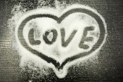 Inscription Love in the heart written with a finger on spilled sugar. Inscription Love in the heart written with a finger on sugar scattered on a wooden dark Royalty Free Stock Photography