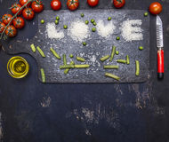 Inscription love, laid out rice on a cutting board with pepper, tomato paste and butter border ,place text on wooden rustic ba Stock Photo