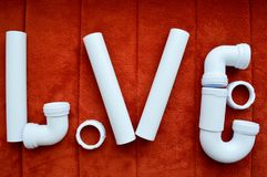 The inscription love is made up of white, plumbing, plastic pipes, fittings, flanges, rubber gaskets Royalty Free Stock Images