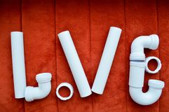 The inscription love is made up of white, plumbing, plastic pipes, fittings, flanges, rubber gaskets Stock Photo