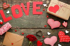 Inscription Love with rose, envelope. And red hearts on grey wooden table Stock Photo