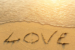 Inscription LOVE on sea beach sand, is soft the wave. Abstract. Royalty Free Stock Photo
