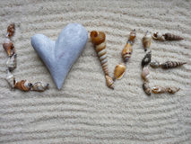 Inscription Love with shells on gray sand - selective focus Royalty Free Stock Photo