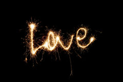 The inscription Love from sparklers. The inscription Love with sparklers on black background Royalty Free Stock Image