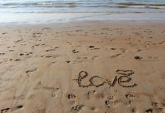 Inscription of `Love` and a symbol of heart in the sand. Footprints in the sand and sea waves at sunset. Inscription of `Love` and a symbol of heart in the sand stock photos