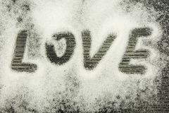 Inscription Love on sugar scattered on a wooden dark background. Inscription Love written with a finger on sugar scattered on a wooden dark background Stock Photography