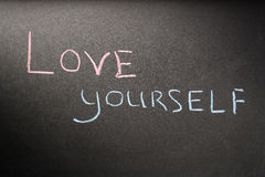 Inscription love yourself. On a dark board with pink and blue chalk royalty free stock images