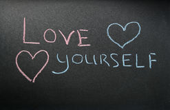Inscription love yourself. On a dark board with pink and blue chalk and two hearts Royalty Free Stock Photography