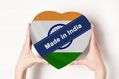 Inscription Made in India, the flag of India. Female hands holding a heart shaped box. White background