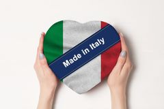 Inscription Made in Italy the flag of Italy. Female hands holding a heart shaped box. White background