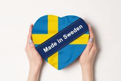 Inscription Made in Sweden the flag of Sweden. Female hands holding a heart shaped box. White background