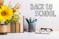The inscription marker on a white board, Back to School. A table with books, a bouquet of flowers, glasses and attributes for