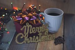 The inscription Marry Christmas and cup of coffee on the tablenn Royalty Free Stock Photos