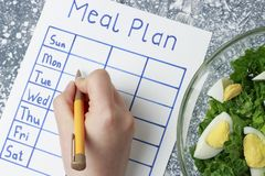 Inscription Meal Plan, schedule on white sheet and whriting hand. View from above. An inscription Meal Plan, schedule on white sheet and whriting hand. View from stock images