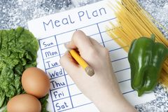 Inscription Meal Plan, schedule on white sheet and whriting hand. View from above. An inscription Meal Plan, schedule on white sheet and whriting hand. View from stock photography