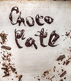 Inscription with melted chocolate on metallic background Royalty Free Stock Photo