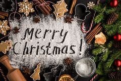 Inscription MERRY CHRISTMAS on powdered sugar background. Inscription MERRY CHRISTMAS on powdered sugar background with fir-tree branches, orange fruits stock photo