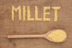 Inscription millet with a wooden spoon on burlap Royalty Free Stock Image