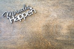Inscription miracles happen on a wooden background. Concept of inspiration and hope. Copy space for your text, top view royalty free stock image