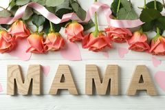 Inscription Mom with pink roses, ribbon and little hearts on wooden background royalty free stock image