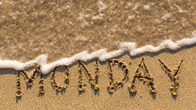 Inscription MONDAY on a gentle beach sand with the soft wave Stock Photography